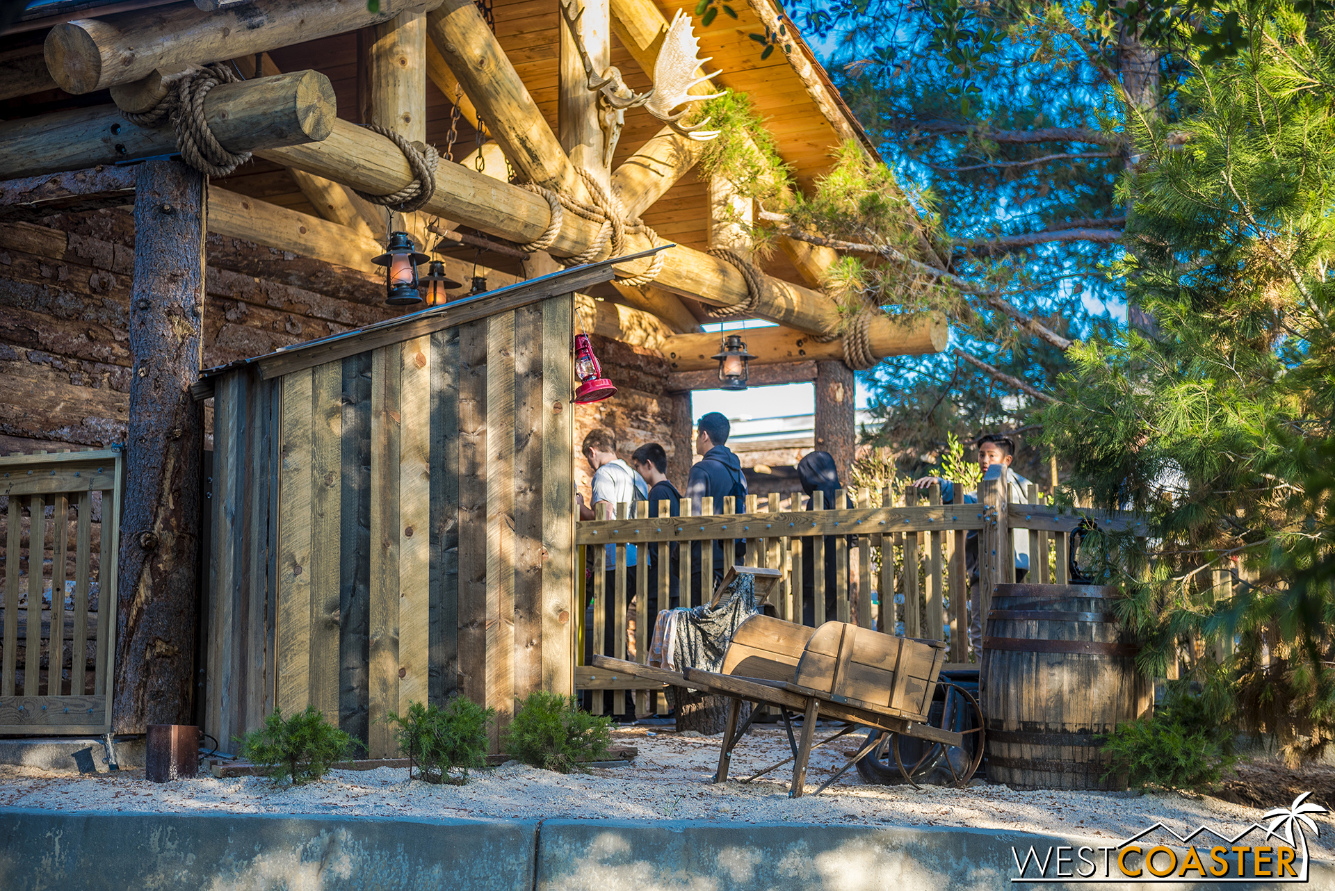 Guests pass by signs of the outpost, like a cart and an outhouse.