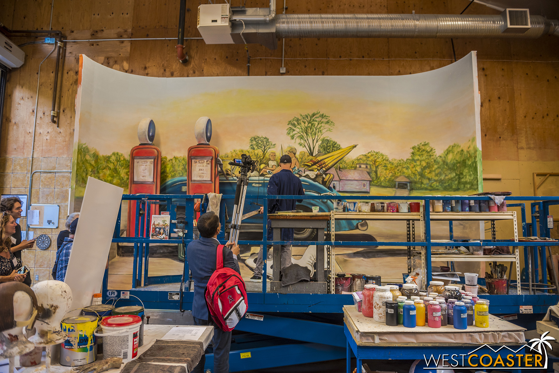 Inside a warehouse, an artist works on a backdrop to one of the paintings that will be recreated.