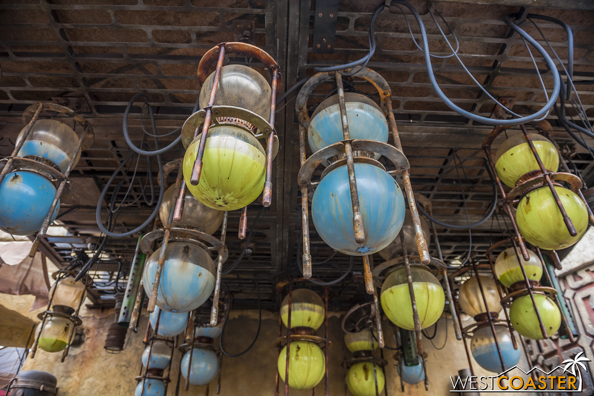 Hanging containers of Blue and Green Milk hang from above, to be dispensed into servings for guests.