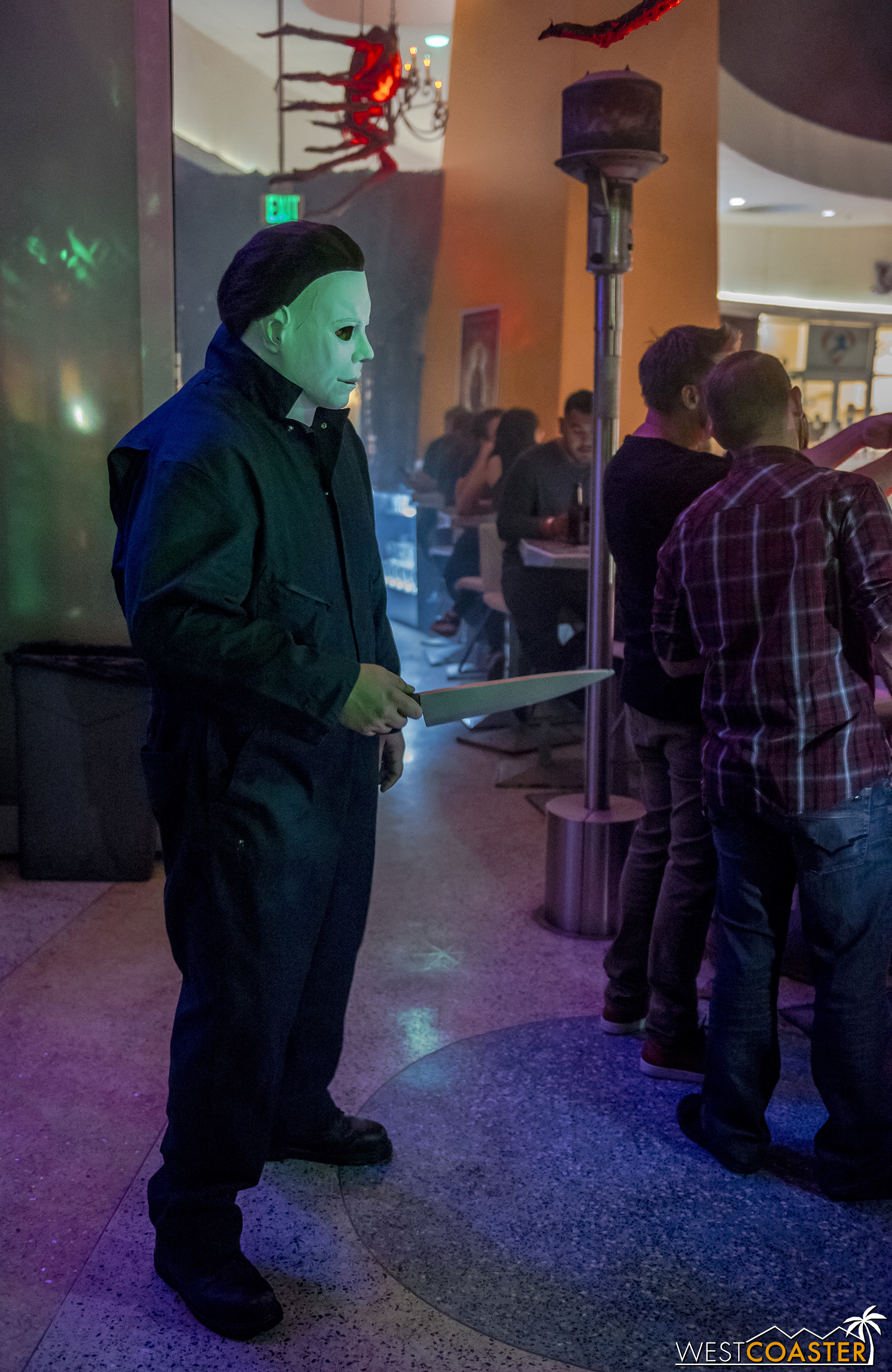 Michael Myers stalks guests but also poses for photos.