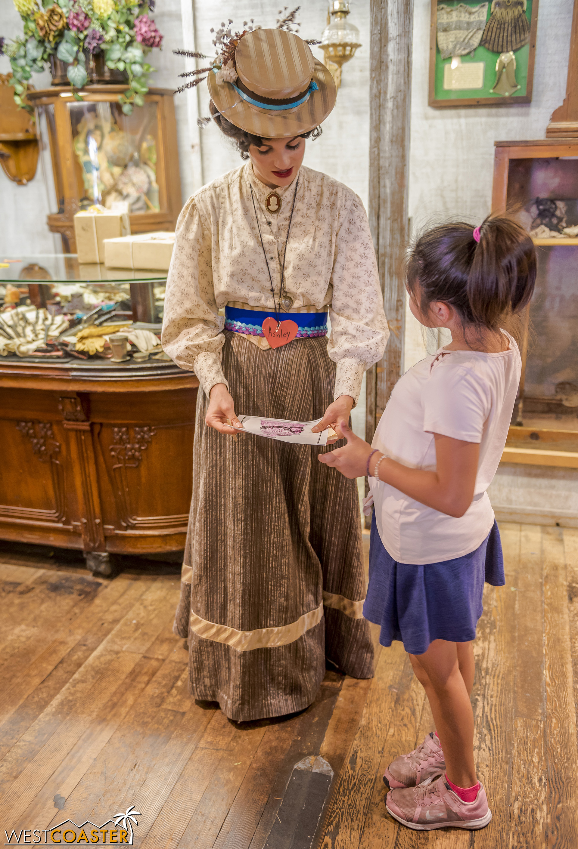 An honorary citizen shows Ashley Kendall a dress design.