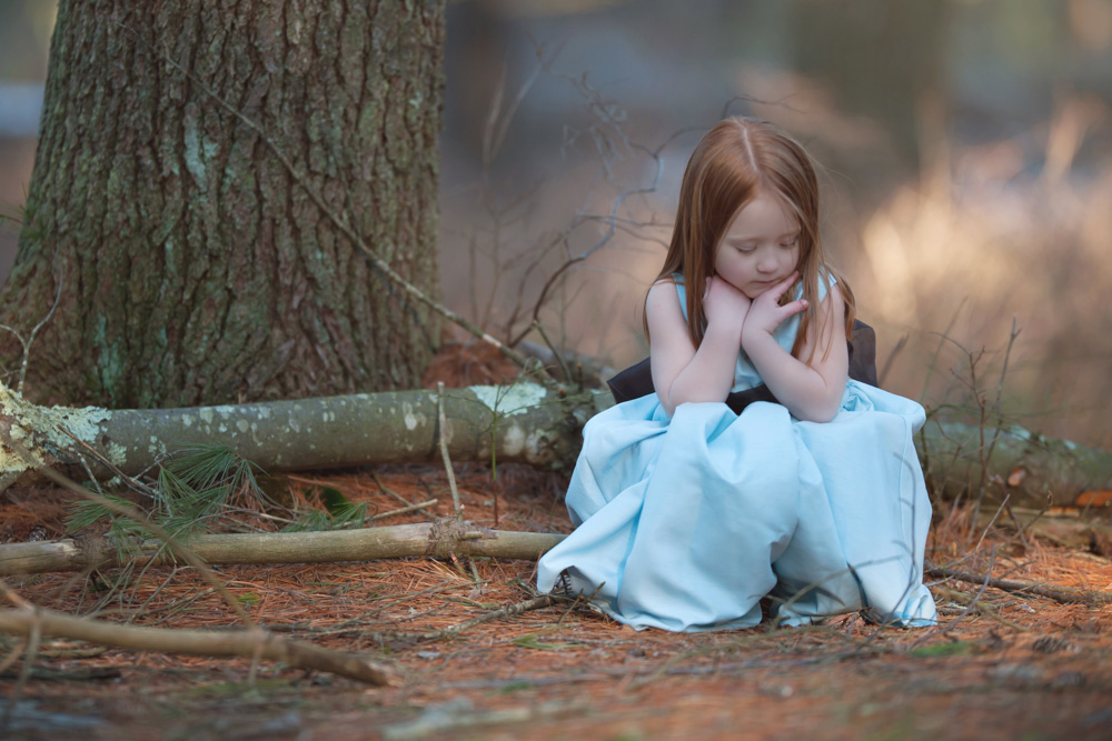 Beautiful little girl sitting and thinking during a styled portr