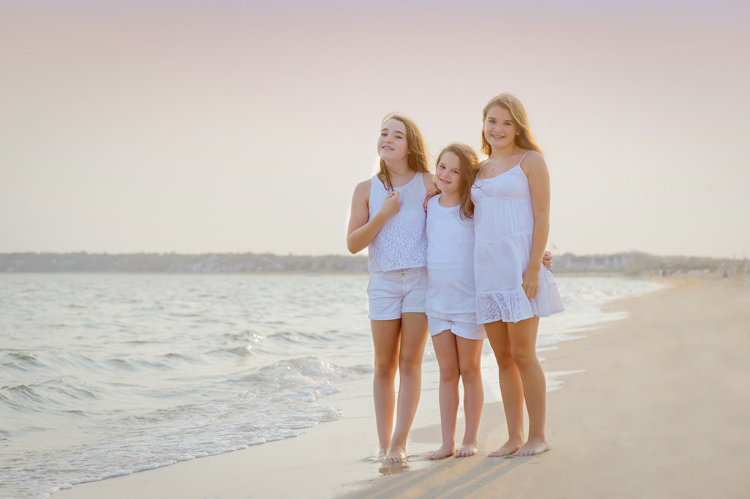 Three Beautiful Sisters standing on the beach and gazing at the