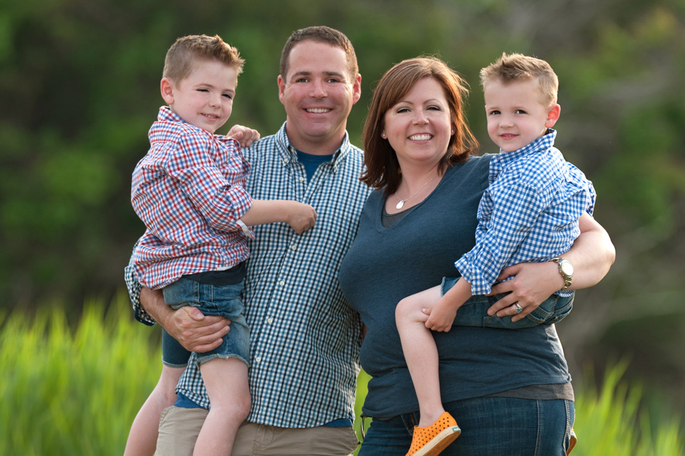 Family of four, 4, posing for family photo in a grassy meadow in