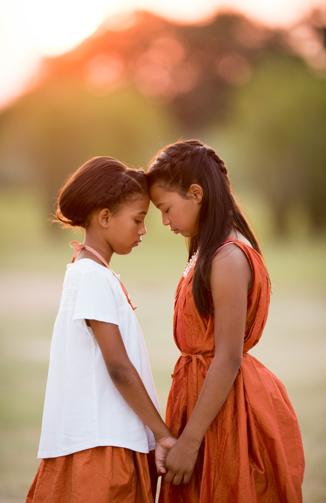 Two beautiful african american sisters leaning together during s