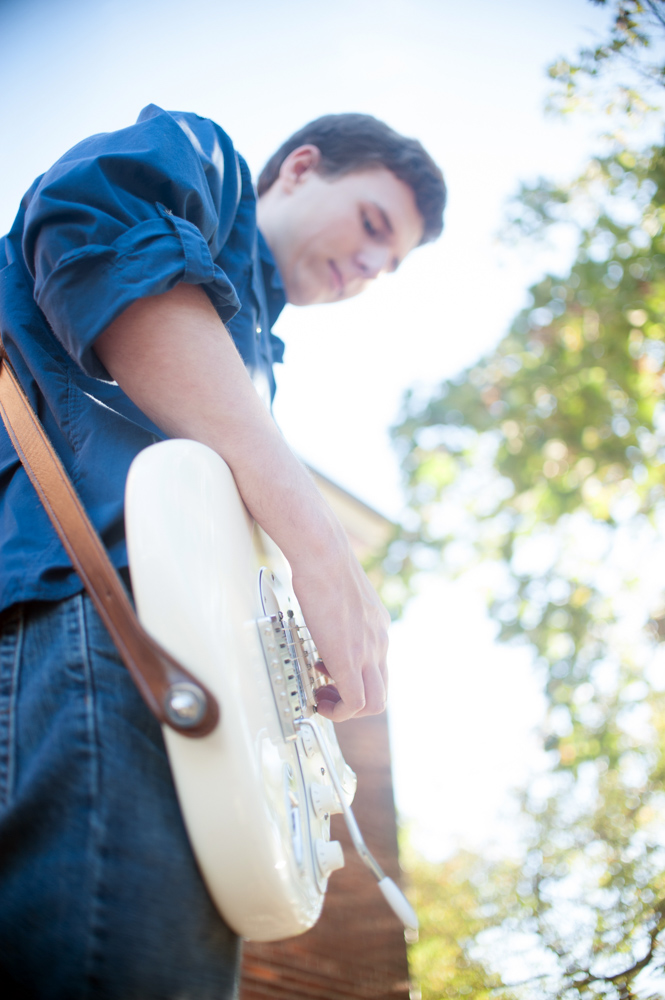 Handsome Young man playing guitar during senior portrait session