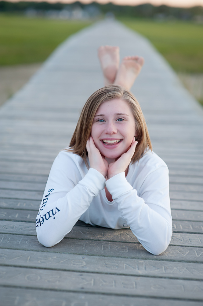 Young tween laying on boardwalk in Sandwich MA at Sunset