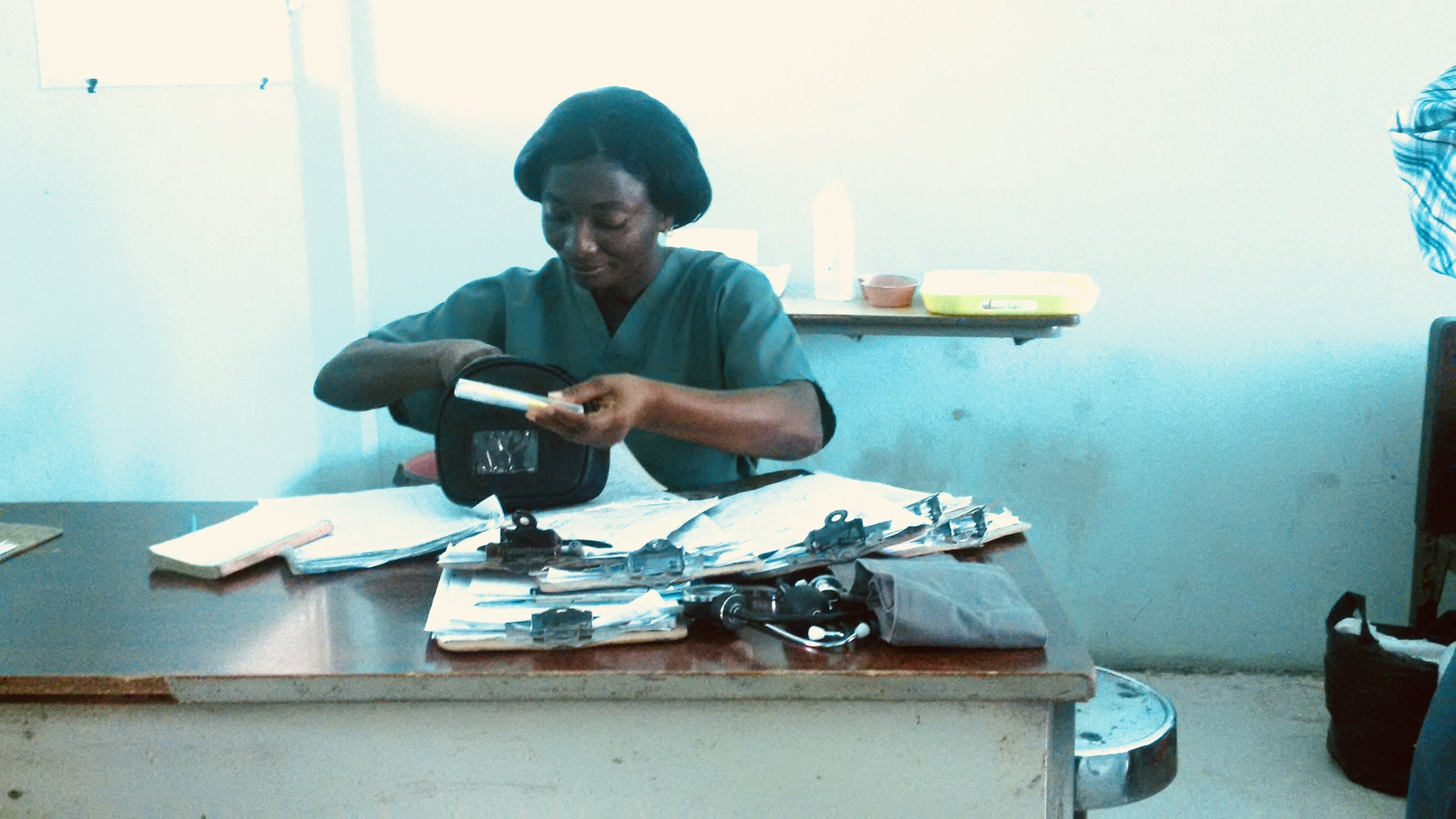 Midwife in Hinche, Haiti with her pile of charts on clipboards. The midwives loved when the volunteers would do their rounds so they could catch up on paperwork. We loved doing patient care all day and not having to chart at all.