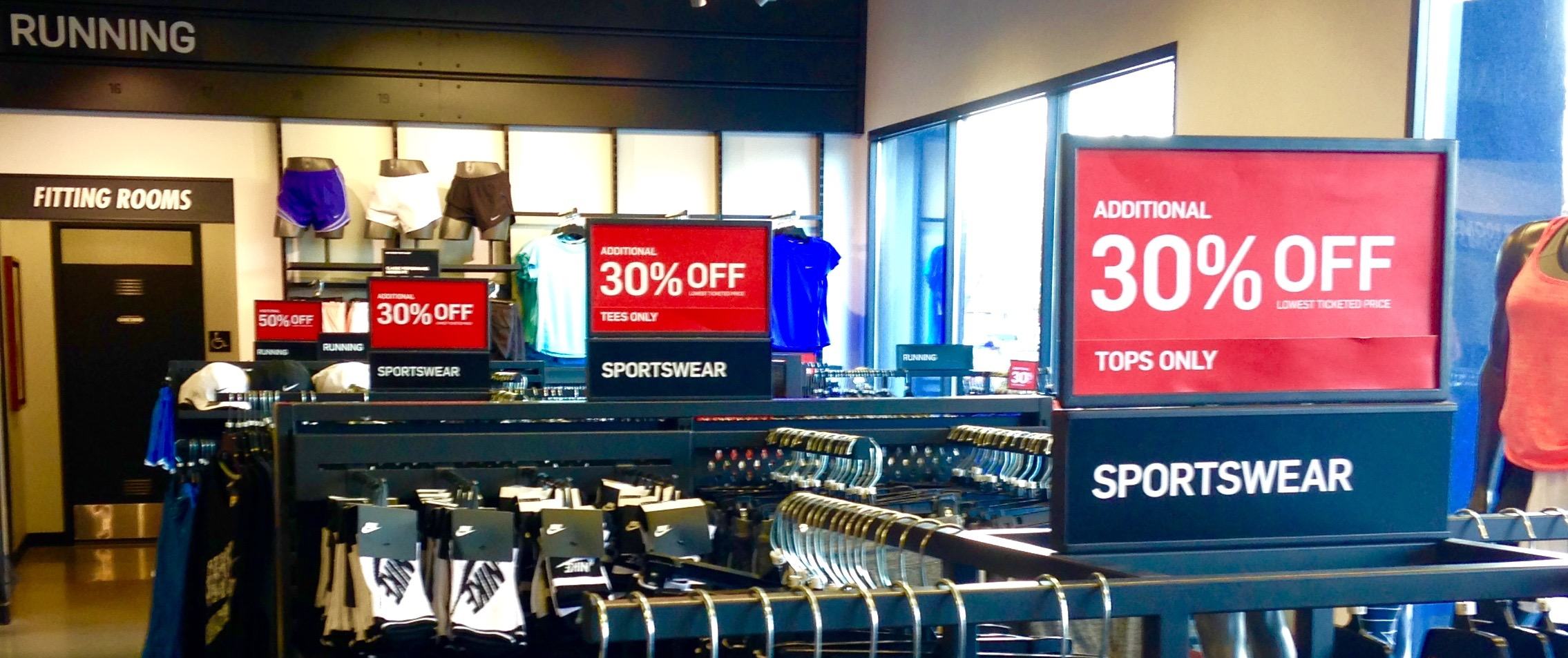 Look for the racks with these red signs, they contain the best deals at the Nike Factory Store. (Apologies for the low quality photo.)
