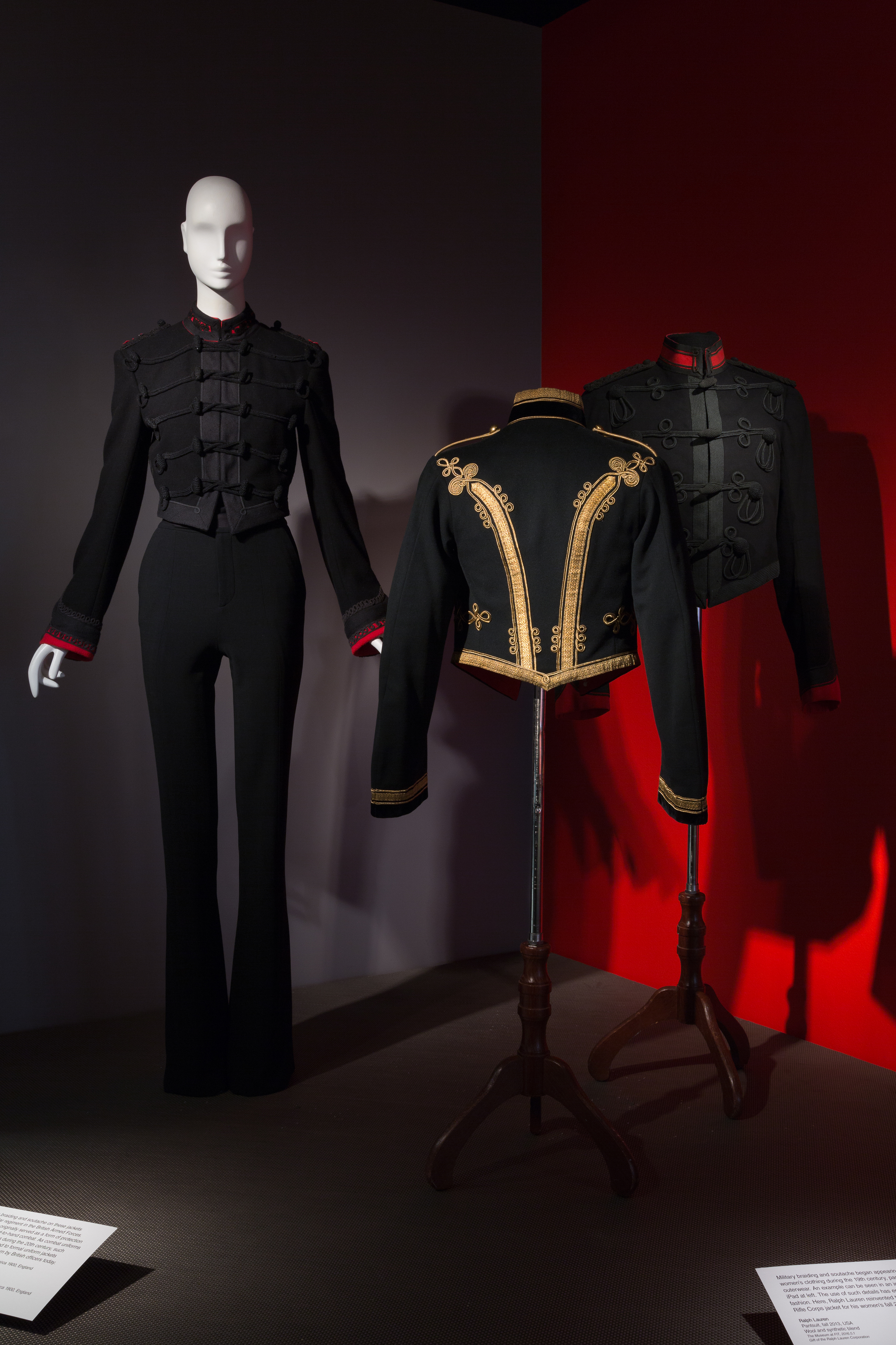 """(left) Ralph Lauren, """"pantsuit,"""" Fall 2013, wool and synthetic blend, USA. Gift of the Ralph Lauren Corporation. (center) Man's Royal Artillery """"mess dress"""" jacket, circa 1900, black and red wool, metallic thread, England. Gift of Adele Simpson. (right) Man's King's Royal Rifle Corps """"mess dress"""" jacket, circa 1900, green wool, red wool, black braid, England. Gift of Adele Simpson. Photo courtesy of Museum at FIT."""
