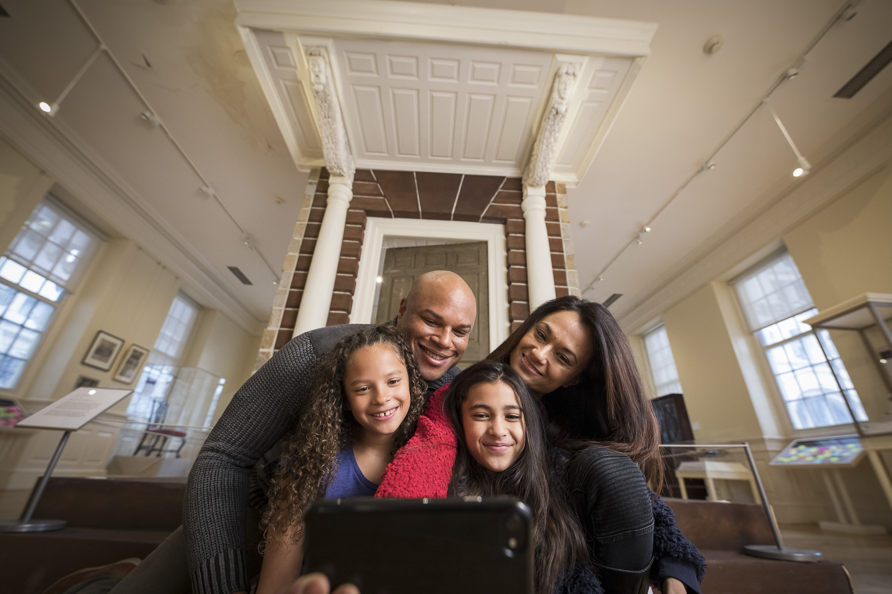 A man and a woman take a selfie with two young girls in front of a door.