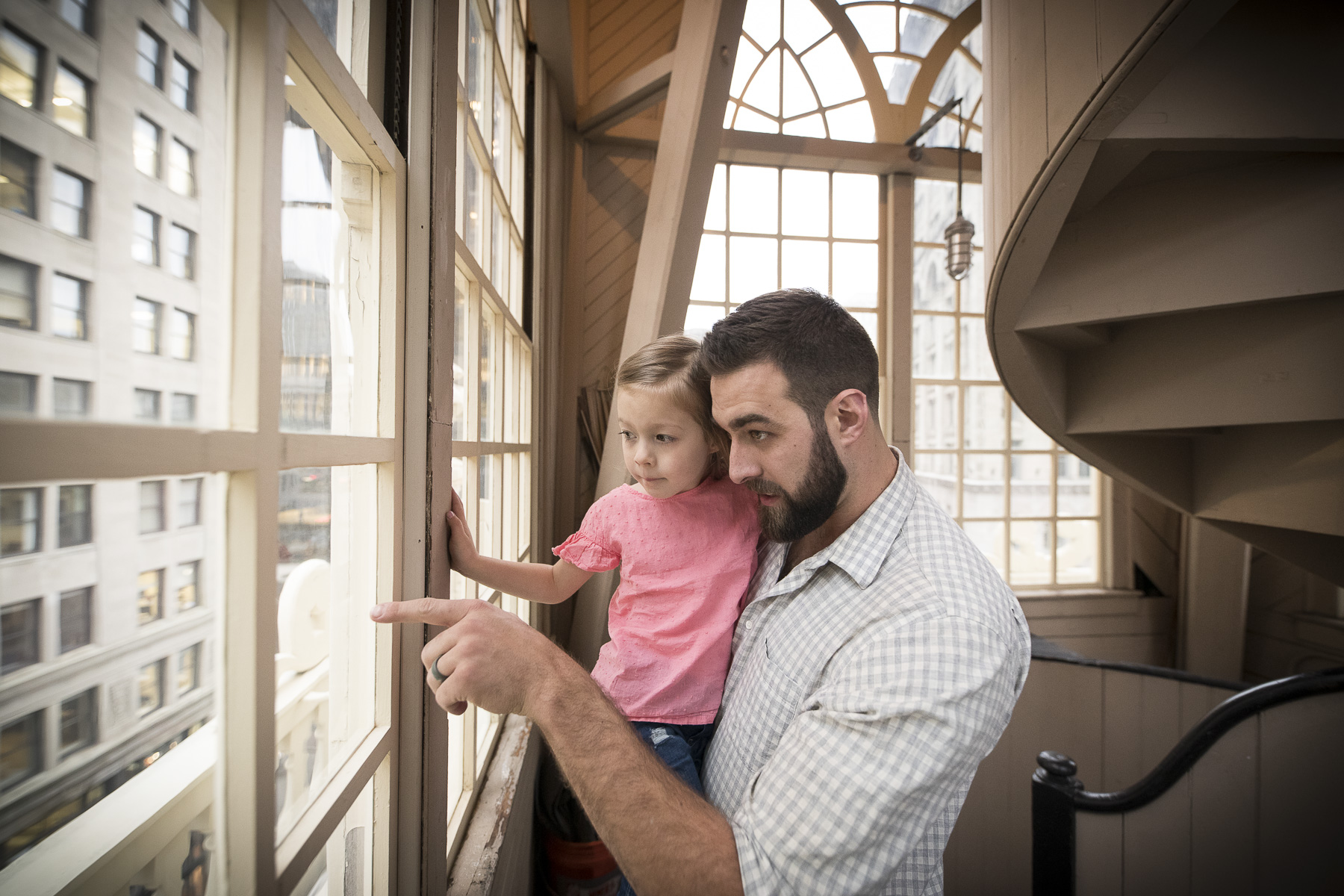 Adult man and toddler girl look out a lattice-work window.