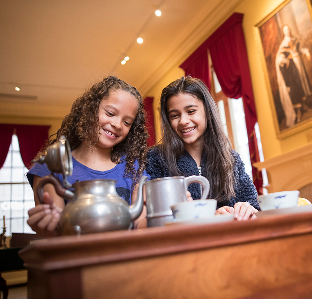 Two young girls examine a tea set on a side table in the Council Chamber.