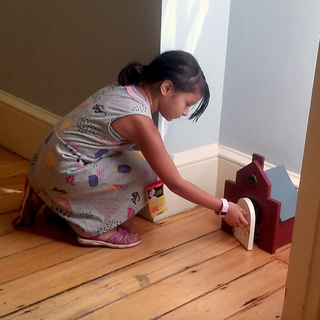 A young girl opens the door on a miniature of the Old State House.