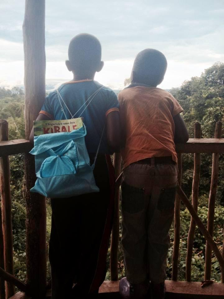 """Ugandan students with their Rutooro edition of """"The Chorus of Kibale"""" on a rainforest field trip."""