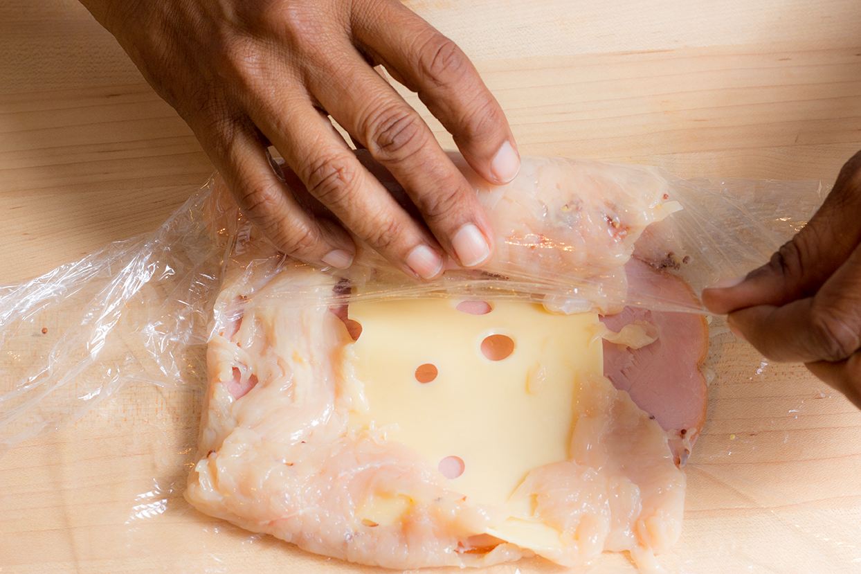Gently lift cling wrap to fold 3 edges of the chicken breast over the ham. On the 4 edge, lift wrap to fold over the edge and then tightly roll the stuffed breast.