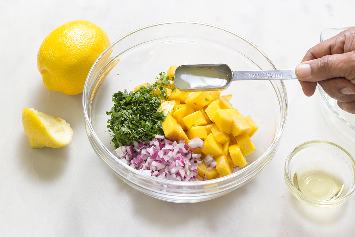 Add lemon juice and zest to chopped mango, cilantro and red onions.