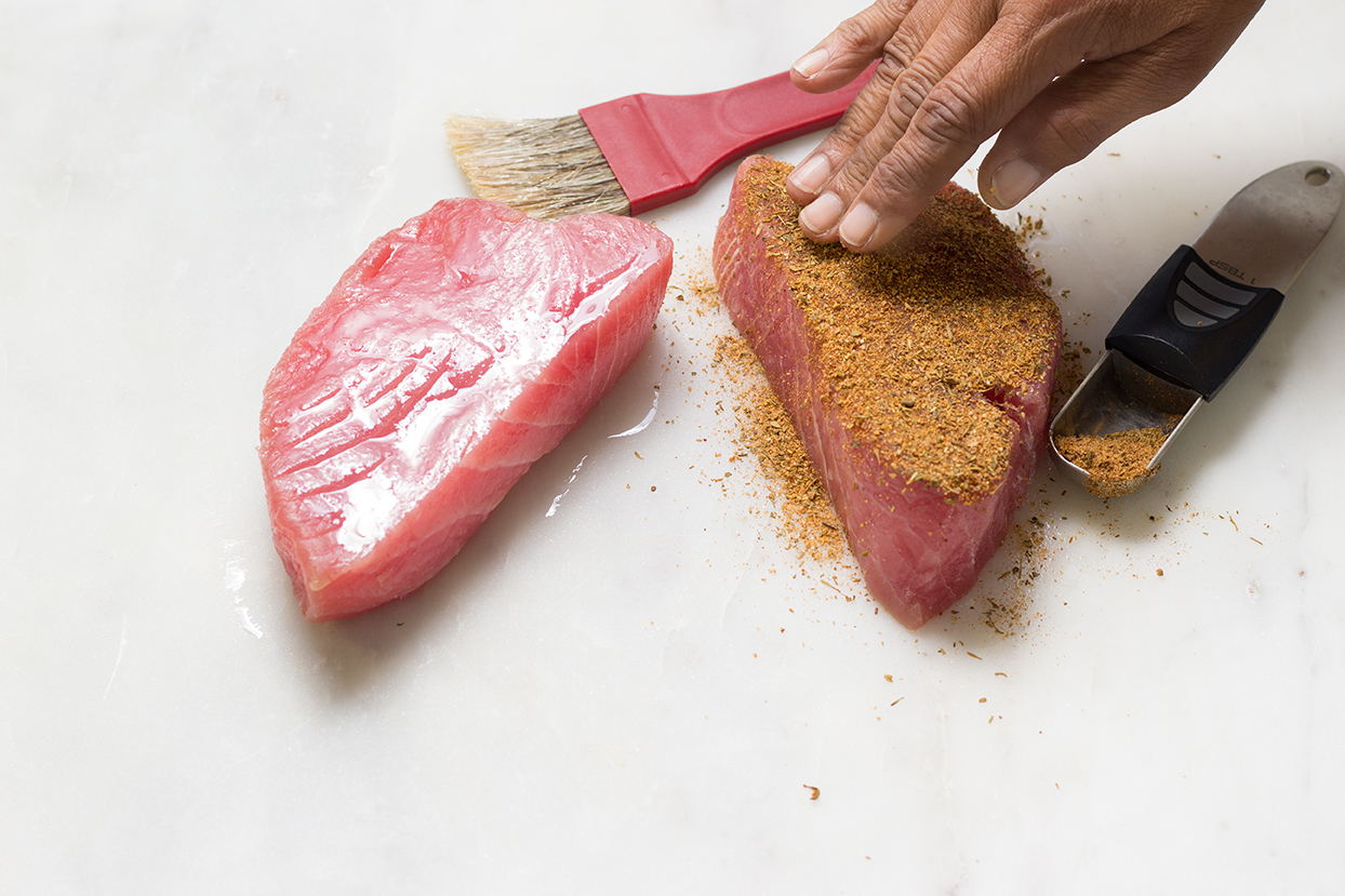 Thoroughly coat top and bottom of tuna steaks with blackened seasoning.  Set aside in refrigerator.