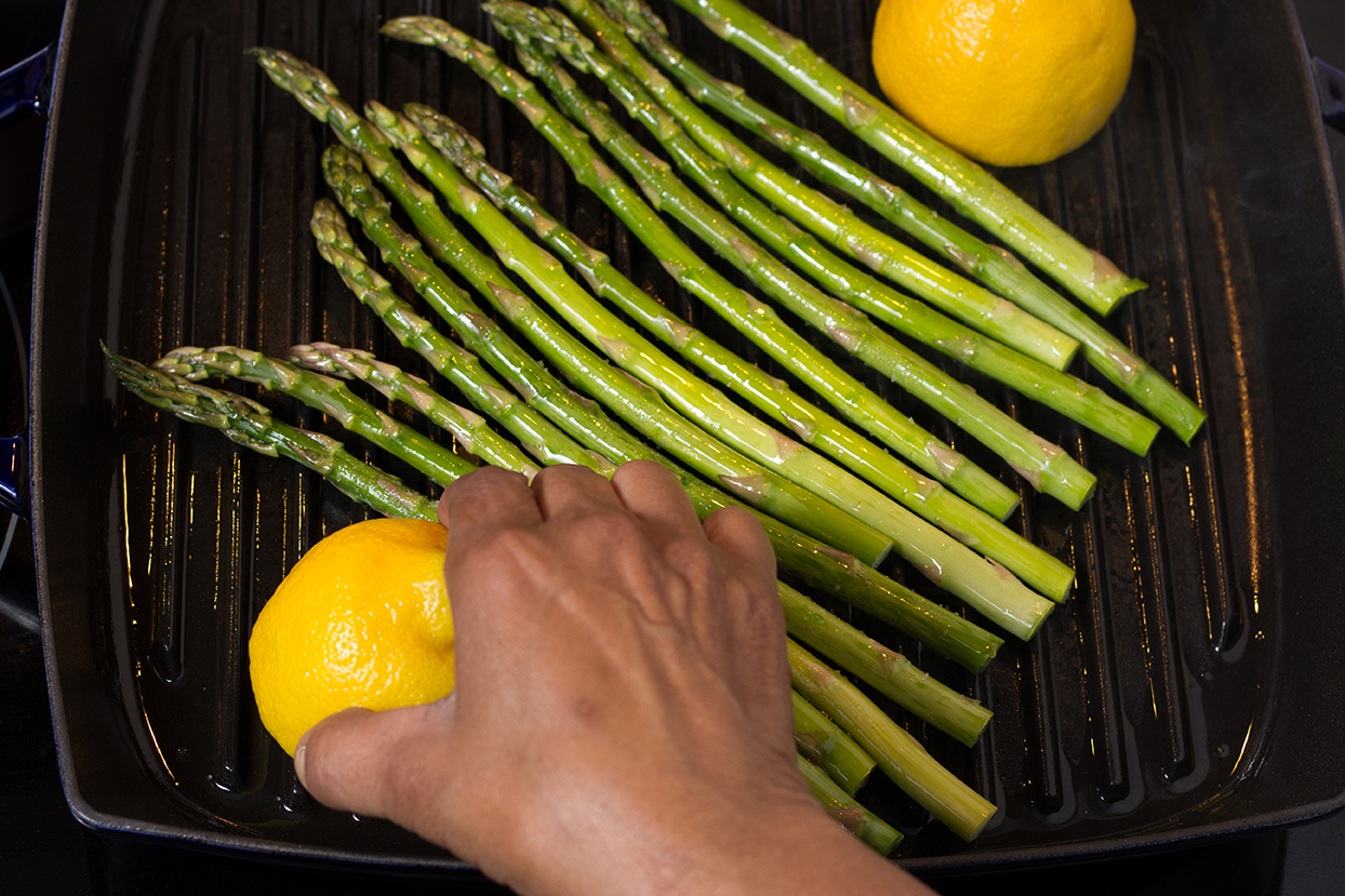 Add asparagus to center of a very hot grill pan.  Cook for 4 minutes on one side.  Grill cut lemons (optional).