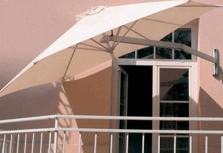 I'm not an affiliate but you can start your search for a wall-mounted outdoor umbrella at   Houzz  .