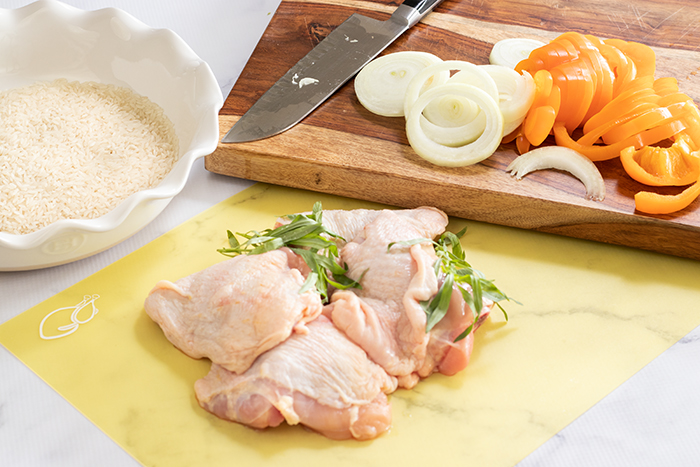 Raw chicken thighs with fresh tarragon, rice and vegetables