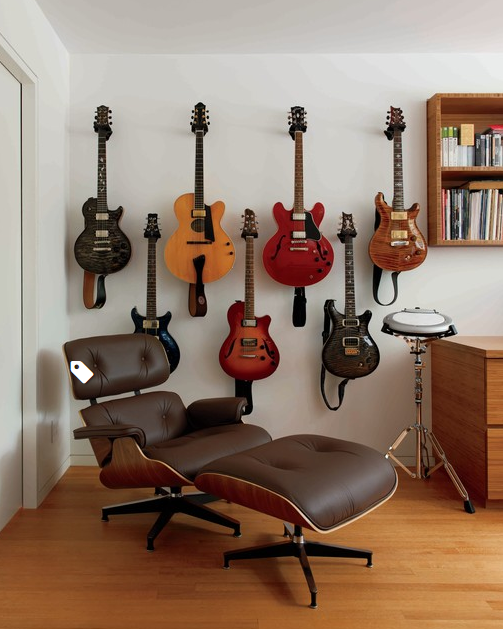 collection of guitars on wall   source