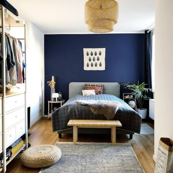 Blue accented wall in bedroom   source