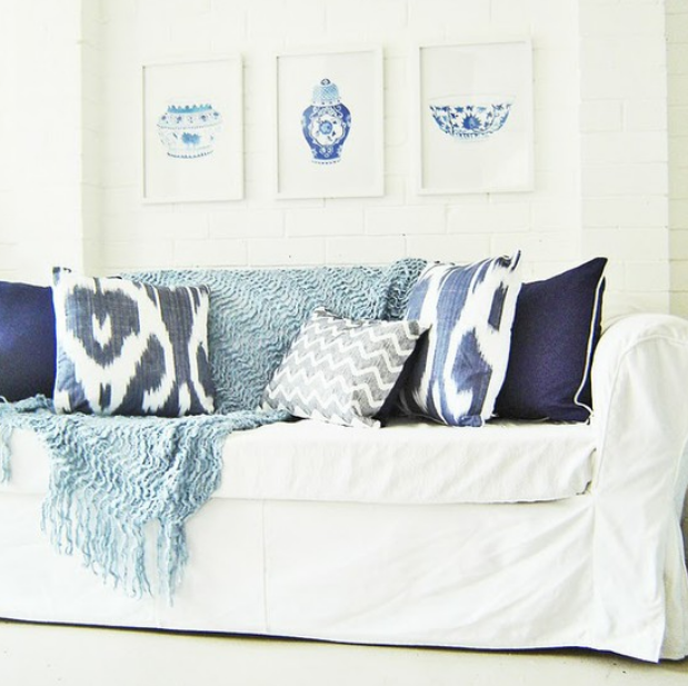 White slipcovered sofa with blue accents   source