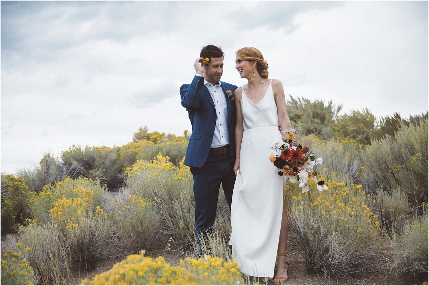 A bride and groom holding their wedding flowers at Brasada Ranch for their wedding.