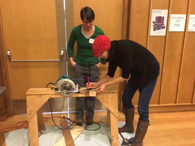 Aviva Krauthammer learns to use a circular saw from Jessica at the Silver Spring Timebank Skills Share in January 2017.