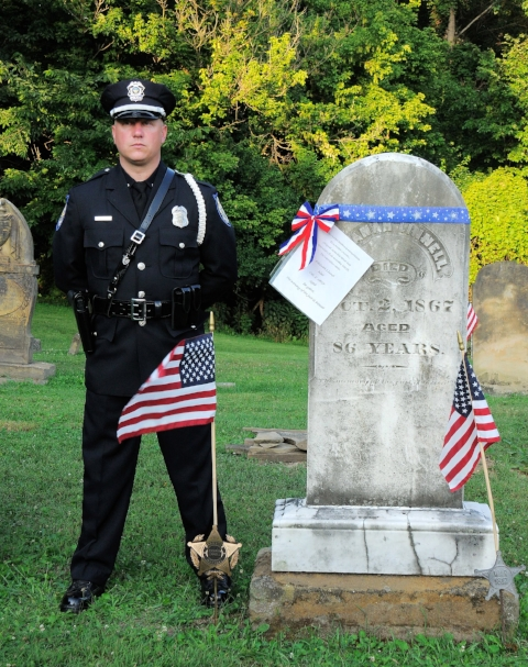 Officer Justin Woodyard stands vigil at the grave of Elkannah Linnell, the first Village Marshal.