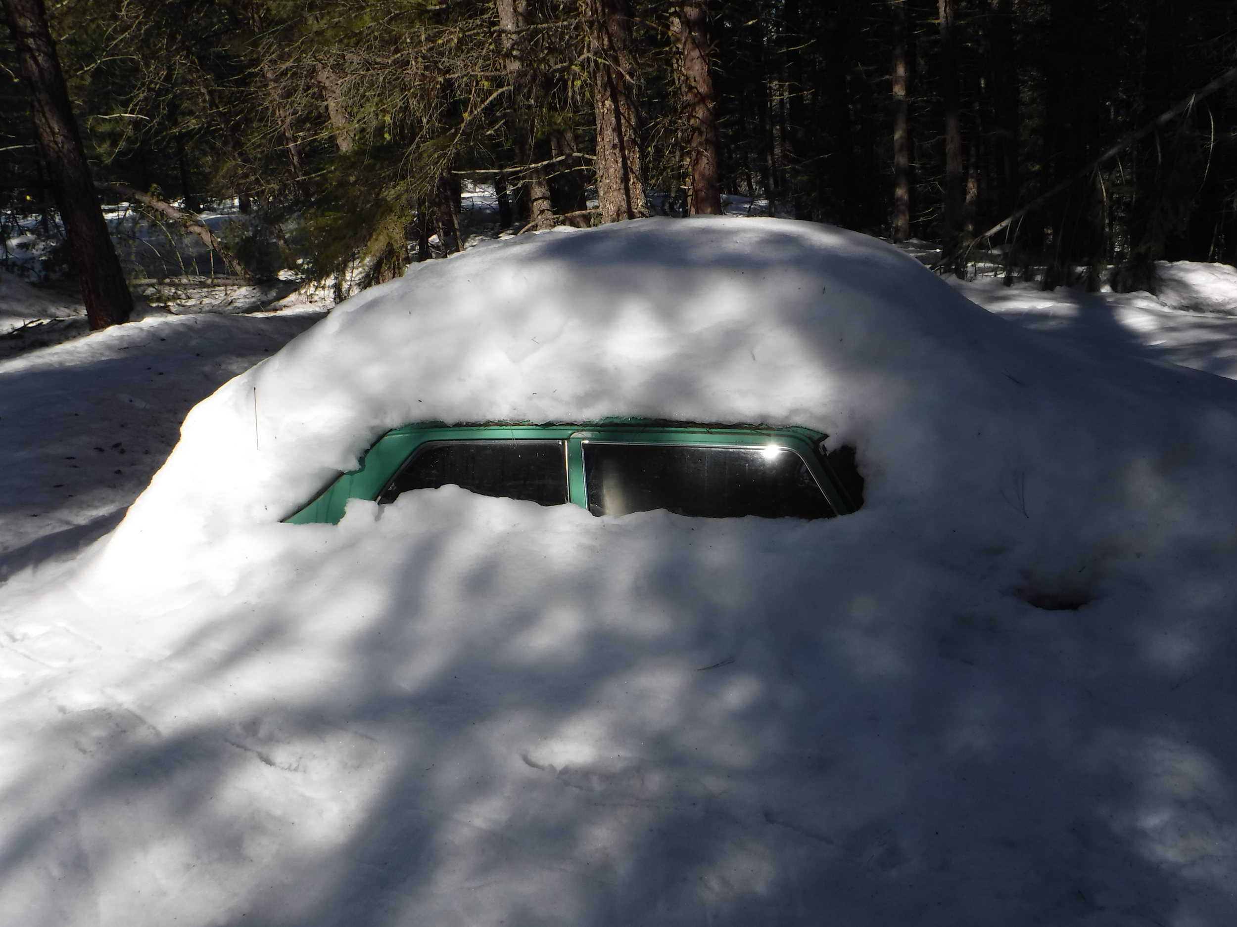 Car left last fall covered in snow. The snow was at least two feet deep.