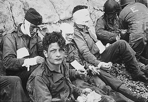 Photo by  The U.S. Army : Soldiers of the 16th Infantry Regiment, wounded while storming Omaha Beach, wait by the chalk cliffs for evacuation to a field hospital for treatment, D-Day, June 6, 1944.  www.army.mil/d-day