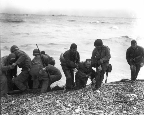 Photo by  The U.S. Army : Members of a landing party help injured Soldiers to safety on Utah Beach during the Allied Invasion of Europe on D-Day, June 6, 1944.  www.army.mil/d-day