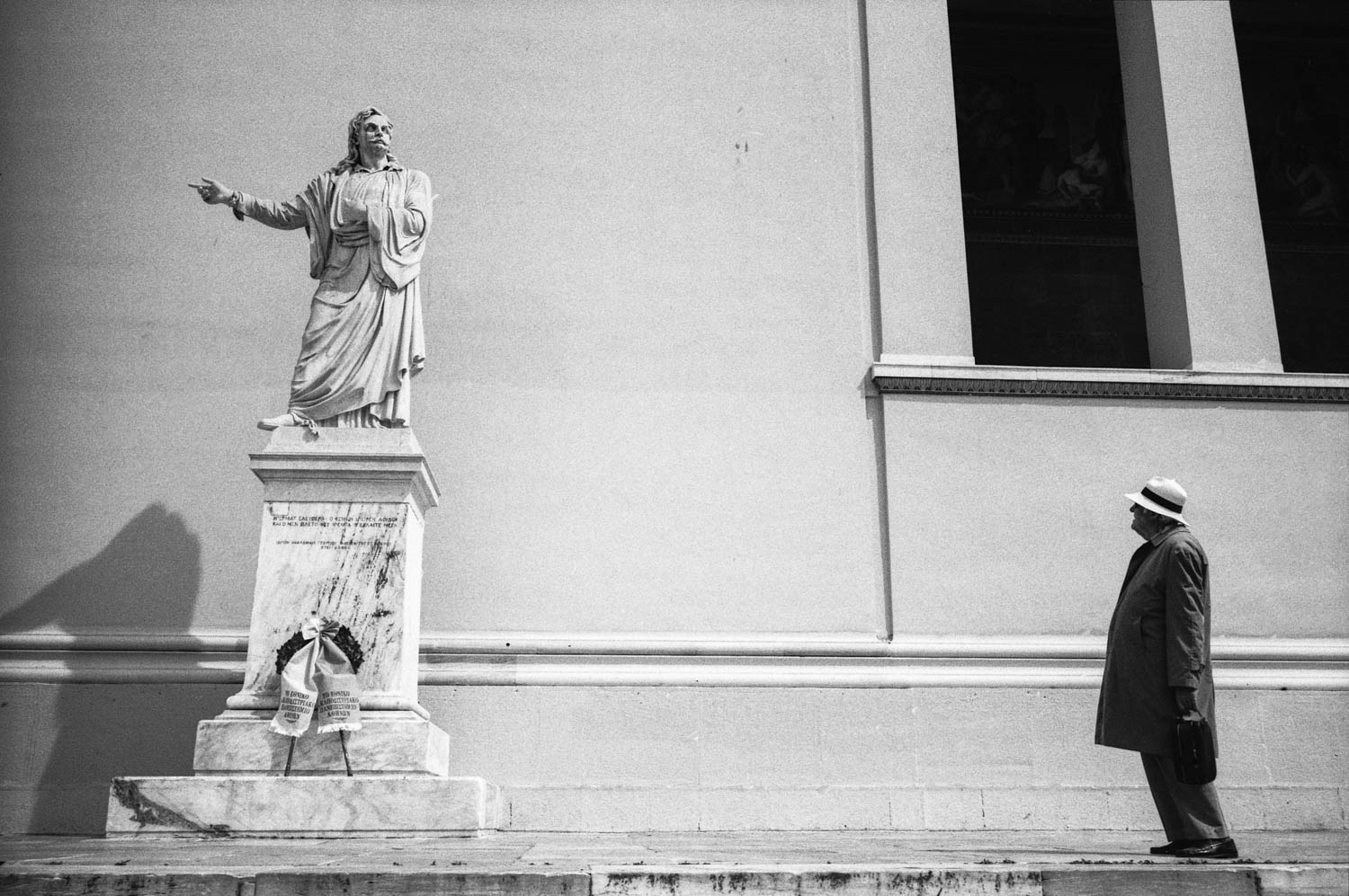 A man stares at a statue on Acadimias Avenue in central Athens