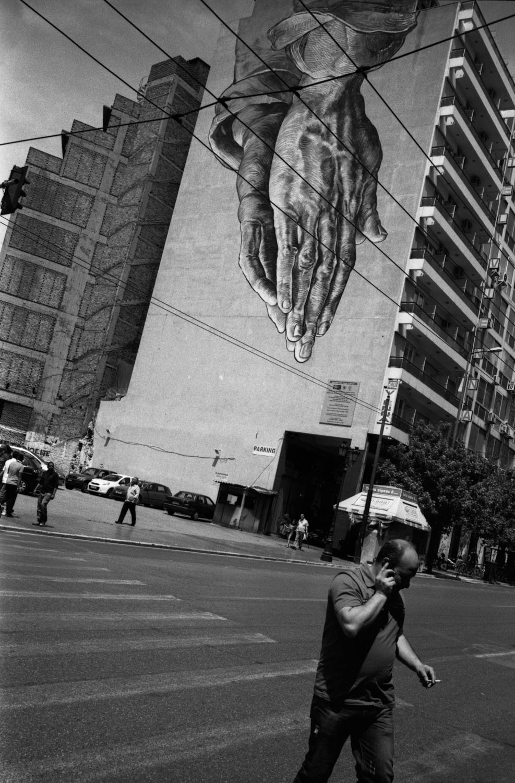 A man walks across Pireas street adorned by Manolis Anastasakos Praying Hands graffiti