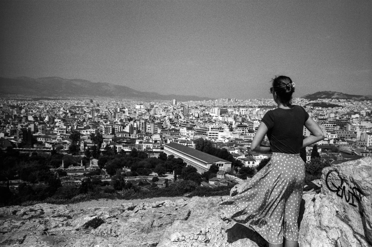 A tourist observes a panoramic view of Athens from the hight of the Acropolis.