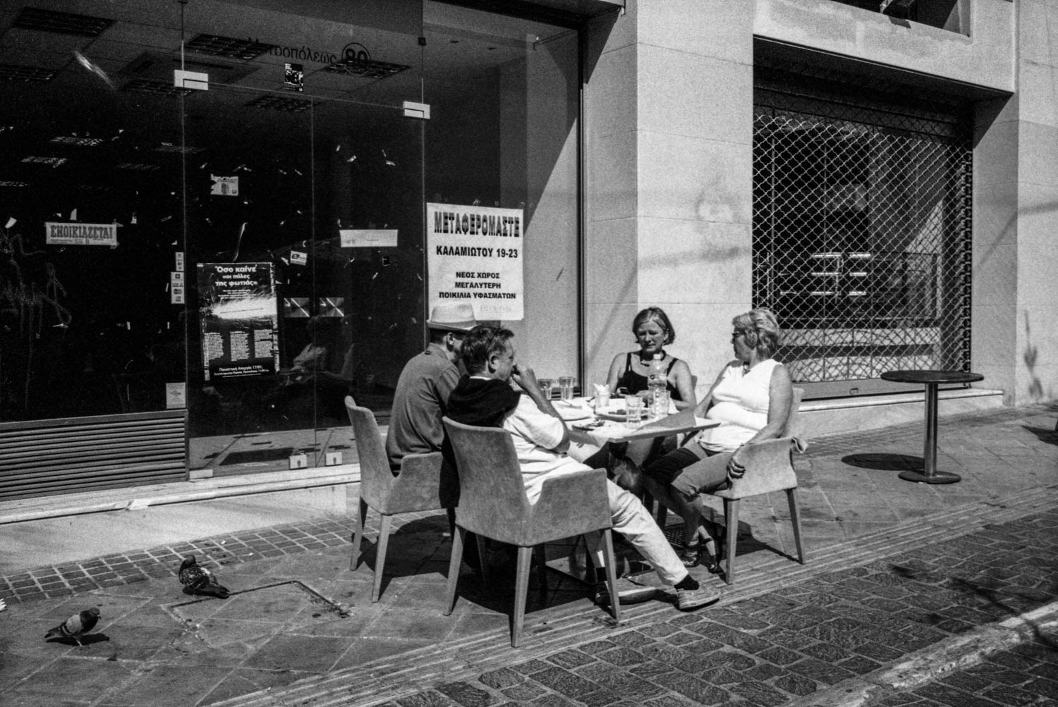 A group of tourists seat around a table of a restaurant in central Athens surrounded by closed-down business.