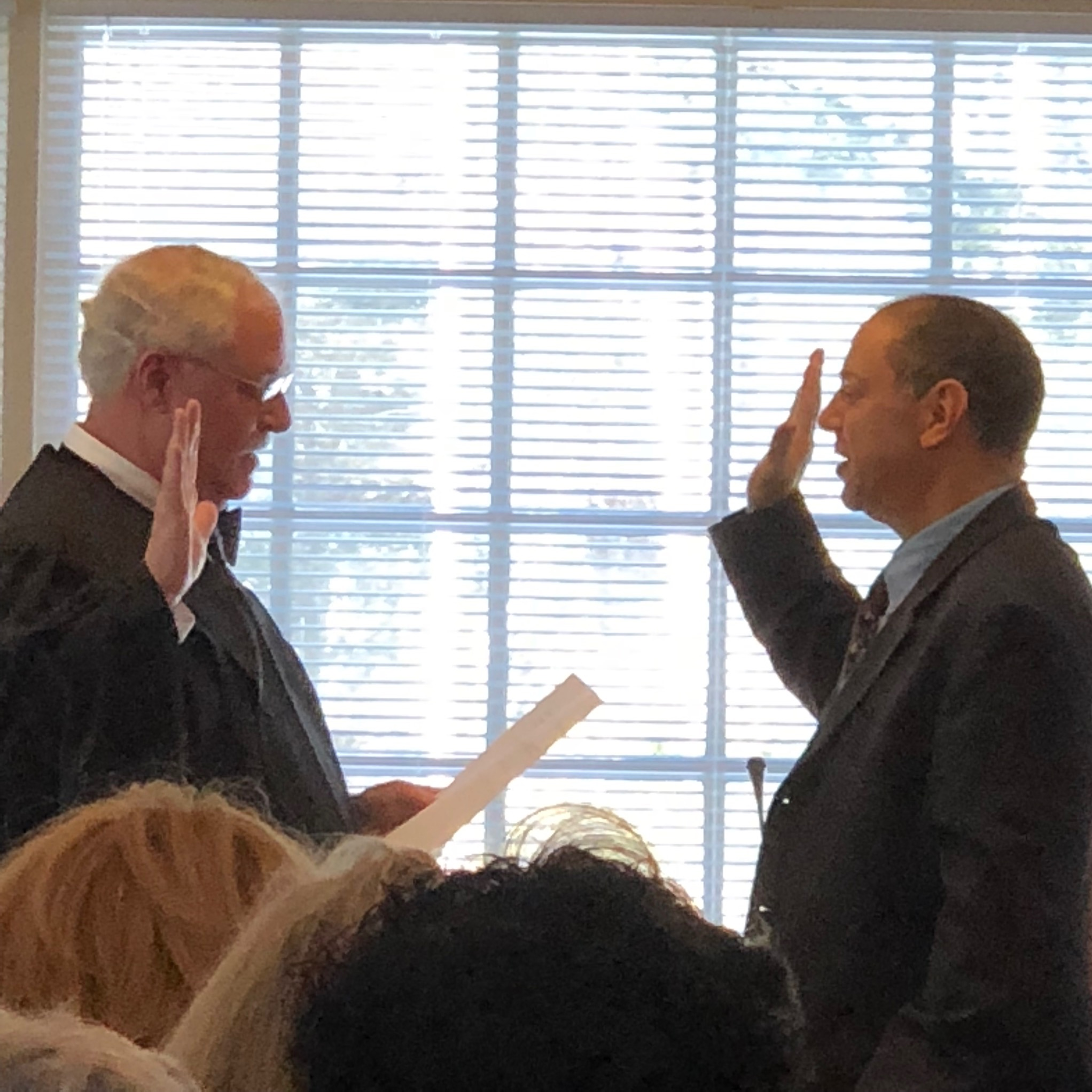 Town Justice Ira Clair swears in reelected incumbent Dan Paschkes as a Town Board member.