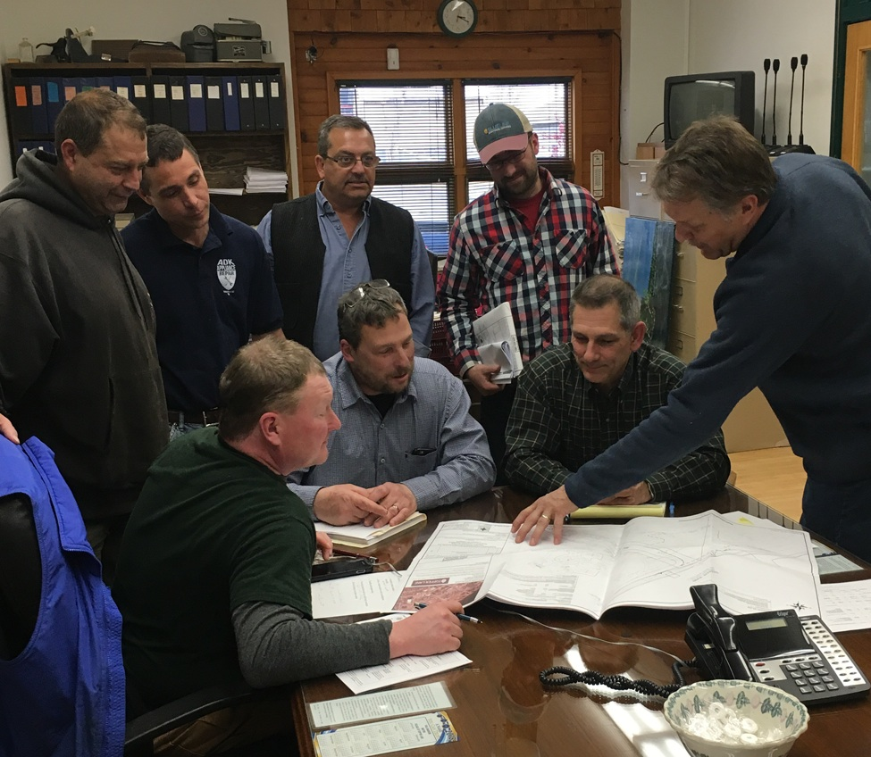 """Contractor and clerk of the works Tom LaMere reviews construction plans with some of the people who will be involved with the building of the new bandshell in Flanders Park at a construction meeting in the village office early last week. From left standing are Excavating Contractor Mark """"Chip"""" Lemieux, Trustee Ron LaScala, Electric Superintendent Marc Save, and Excavating Contractor Adam Boudreau. Sitting at the board table were Trustee Clint Hollingsworth, Code Enforcement Officer Pete Edward and Engineer Kurt Bedore. (Photo by Katie Stuart)"""