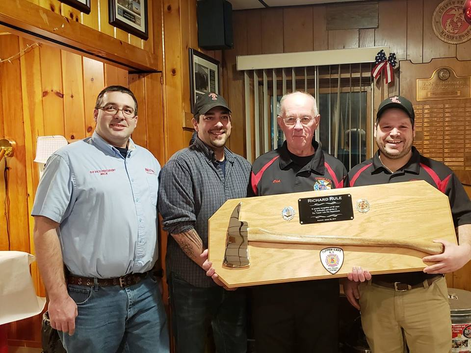"""Major milestone of committed service to the community  An impressive hand-made award sporting a commemorative fire ax and appropriate words depicting the hometown fire department's deep appreciation was given this weekend to Richard """"Dick"""" Rule to mark his half-century of fire service to the community and its citizens. It was awarded at a banquet in his honor. Pictured flanking Dick were First Assistant Chief Nick Rolley, who is also first vice president of FASNY, Chief Royce Cole and Second Assistant Chief Joseph Arsenault. (photo provided)"""