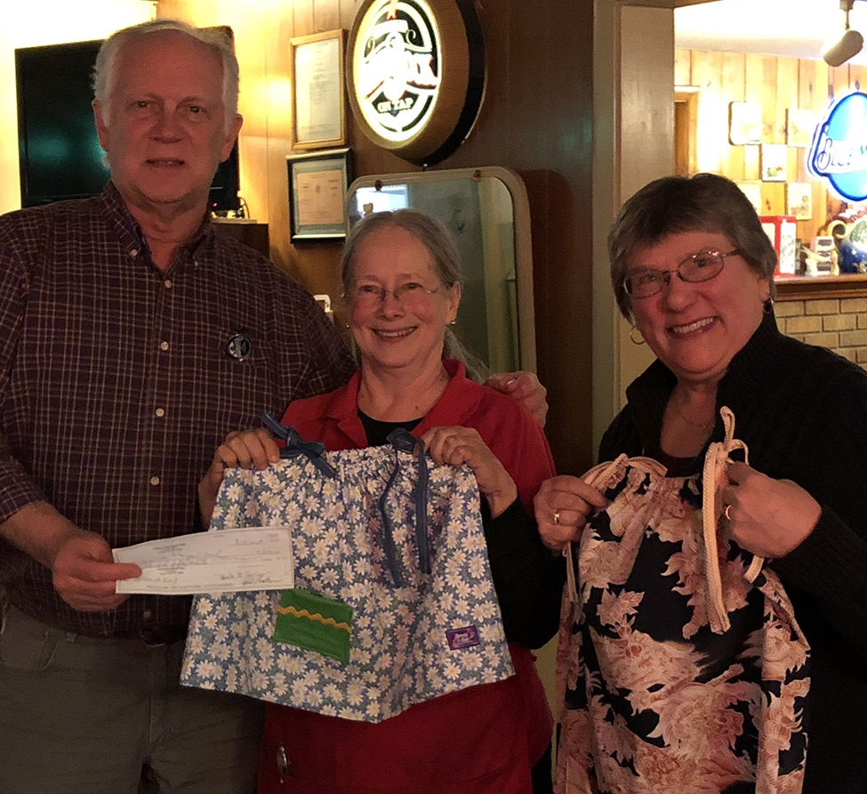 Lions Club past president Stuart Nichols presents a club gift of $250 to help underwrite some of the expenses of the local Dress a Girl chapter. Pine Grove co-owner Donna Philippi and Librarian Peg Mauer hold up two of the dresses local volunteers made recently at a recent Lions Club meeting. (Dan McClelland photo)