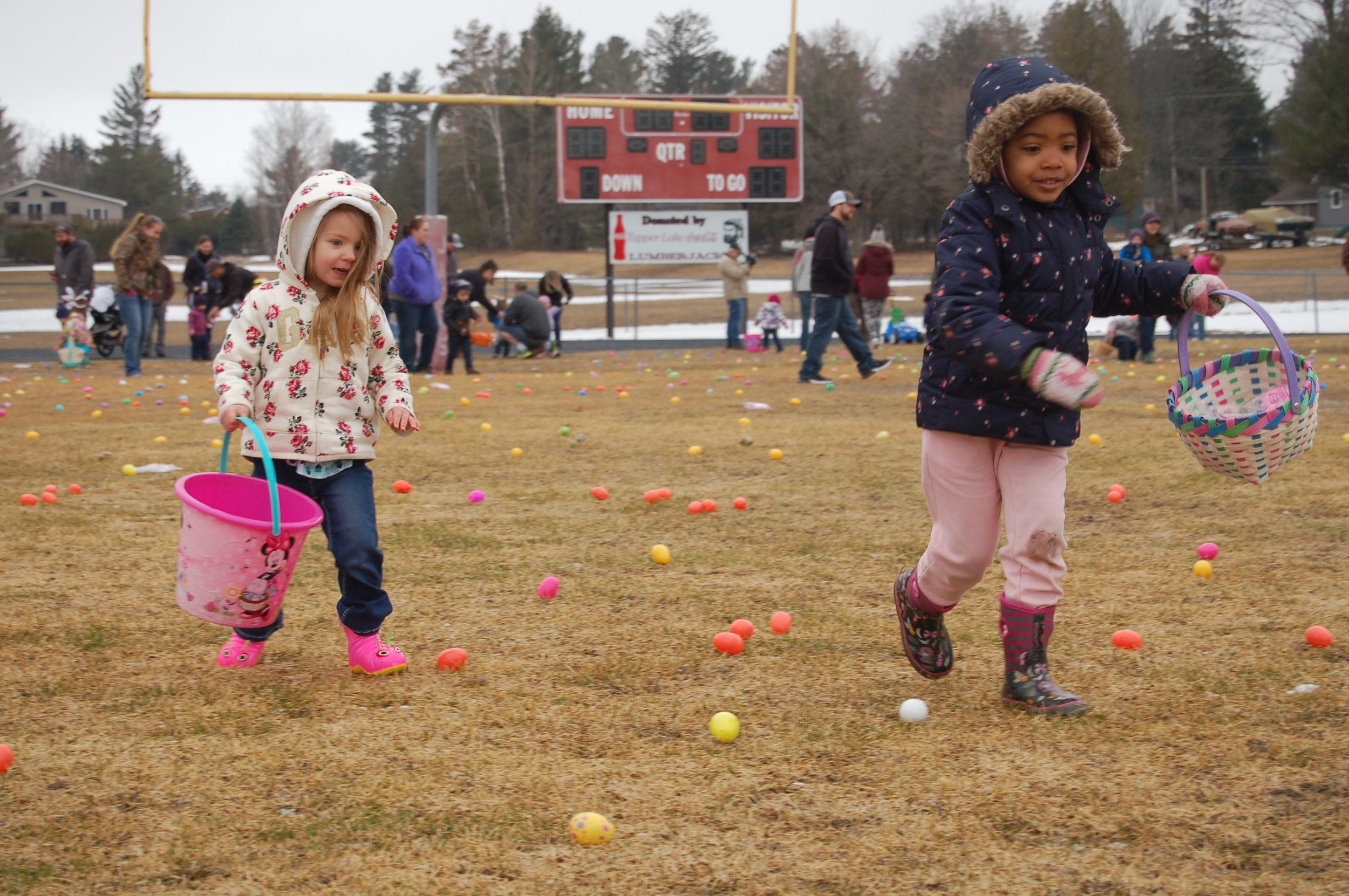 Paisley Silvia and Genevieve Arsenault rush to fill their Easter baskets.