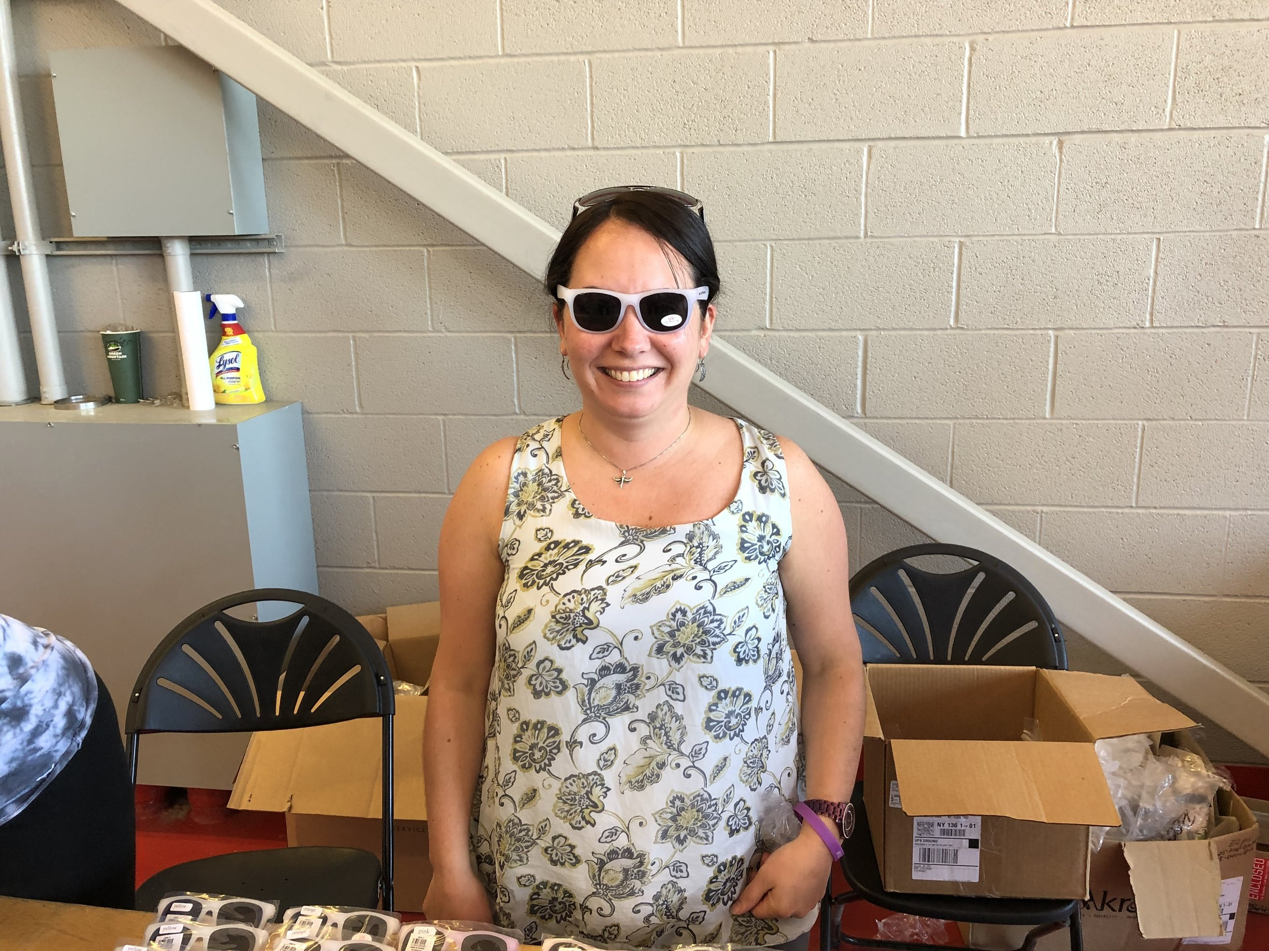 Amanda Amell was one of the volunteers distributing a handful of police department souvenirs including sun glasses, which she was trying on, frisbees, digital wrist lights, water bottles, all that could be carried home in a nice PD bag.