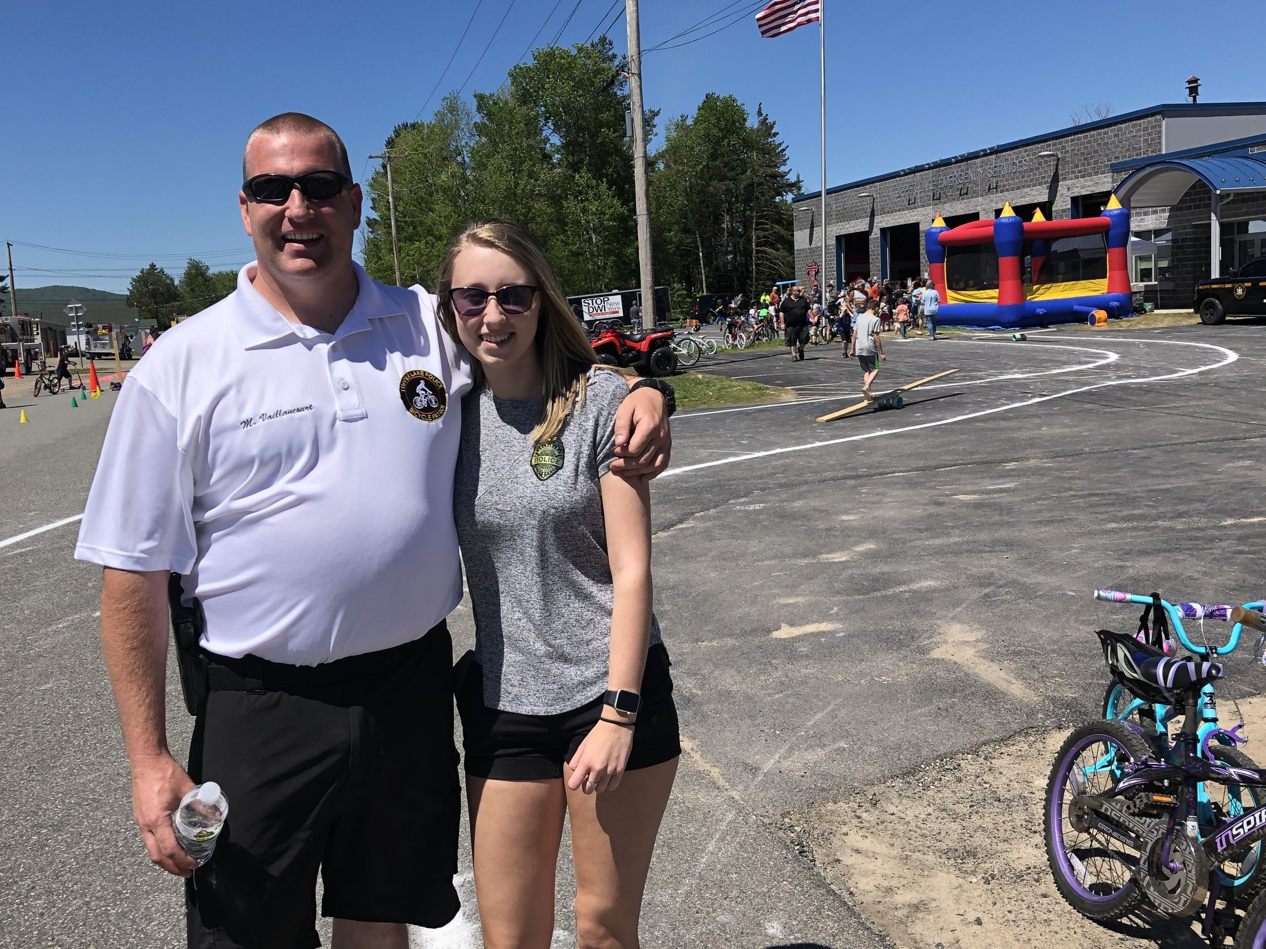 The man who has been the driving force for Tupper Lake's annual Bike Rodeo since 2008, Officer Michael Vaillancourt, was extremely pleased with the great weather Saturday which featured cloudless skies and warm temperatures. Some of Mike's events in the past have met with rain and cool weather, but like the circus, the rodeo always goes on. When things have been really damp in recent years, the event has been moved inside the fire station on Santa Clara Ave.  He poses above half way through the multi-faceted event with high school volunteer, Samantha Higgins, who is in tenth grade. Samantha also helped last year.  Mike said that day he figures total attendance would top 700 that day, when all riders and their family members were figured into the mix.  He said the 60-foot long inflatable obstacle course was a big hit with the kids this year.  New this year too was the Franklin County Sheriff's Department new high-axle transport vehicle, which came from the U.S. military and which will be used in flooding situations, where raging and deep water has to be crossed.