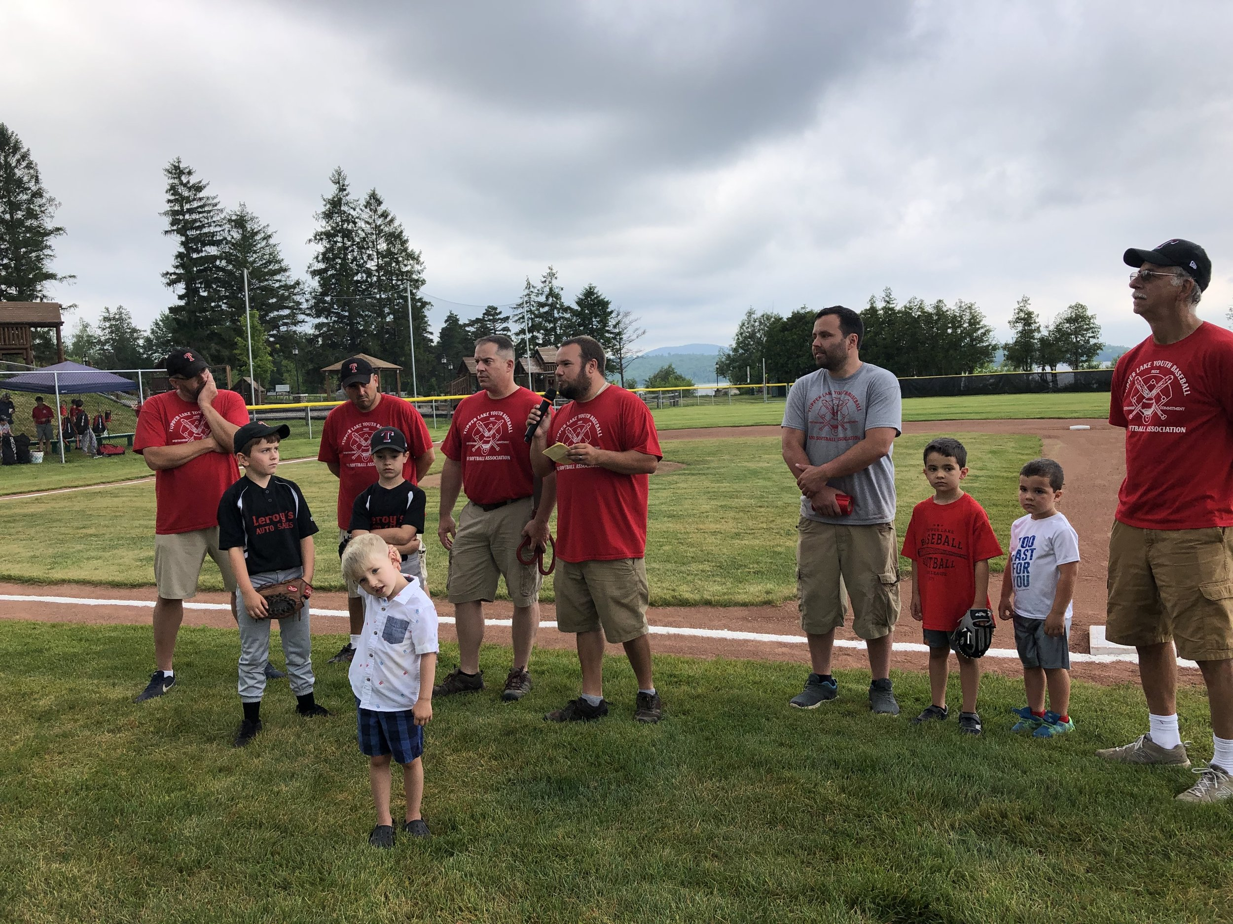 Tupper Lake Youth Softball and Baseball Association president Dan Brown (at center), with his directors and their children, had high praise for all those who helped and all those who contributed to the creation of the new $100,000 plus Little League-sized field in the municipal park.