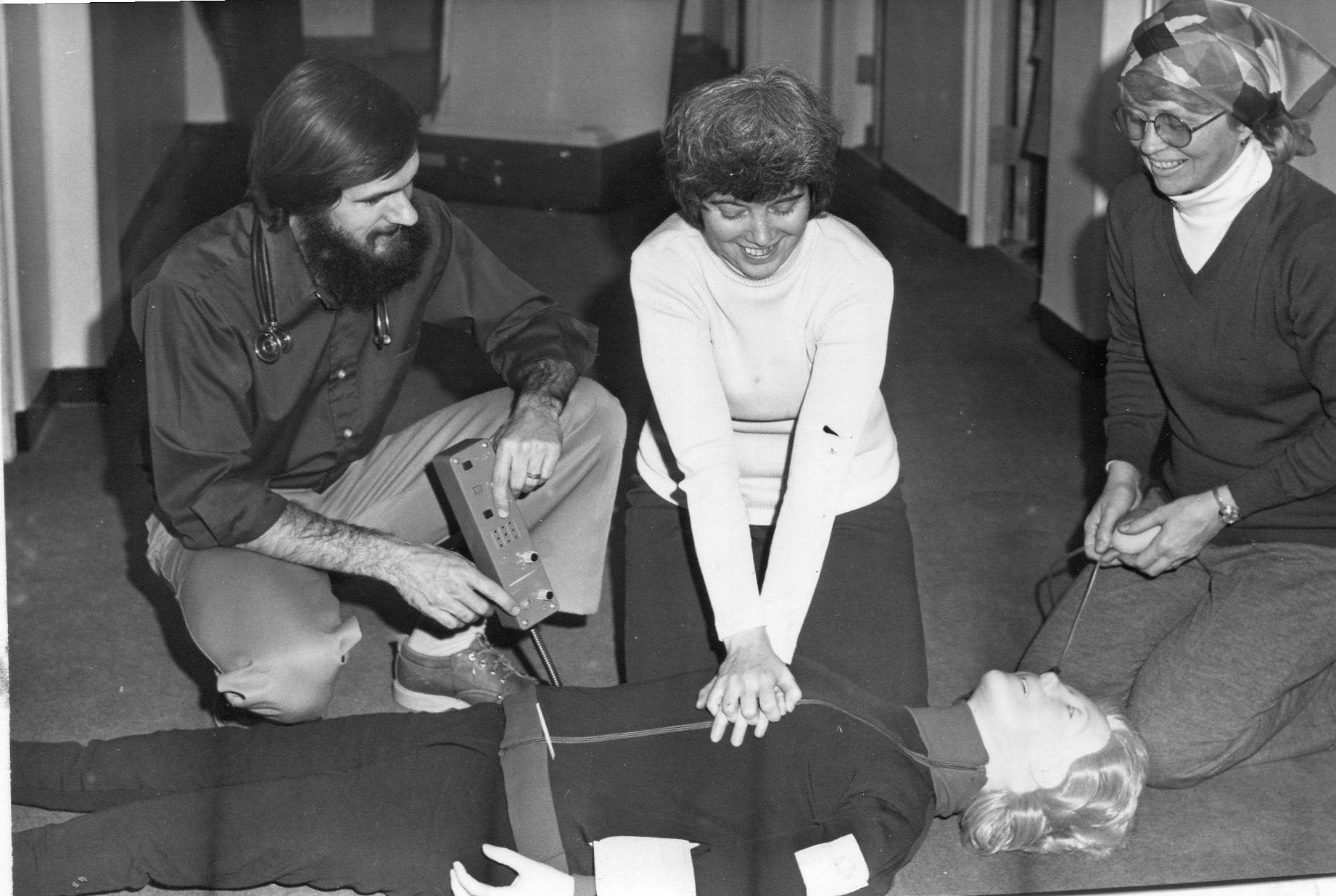 Dr. David Johnson was instructing Carol Merrihew and Jane Johnson on the techniques of CPR with Resuscitation Annie in the 1980s.