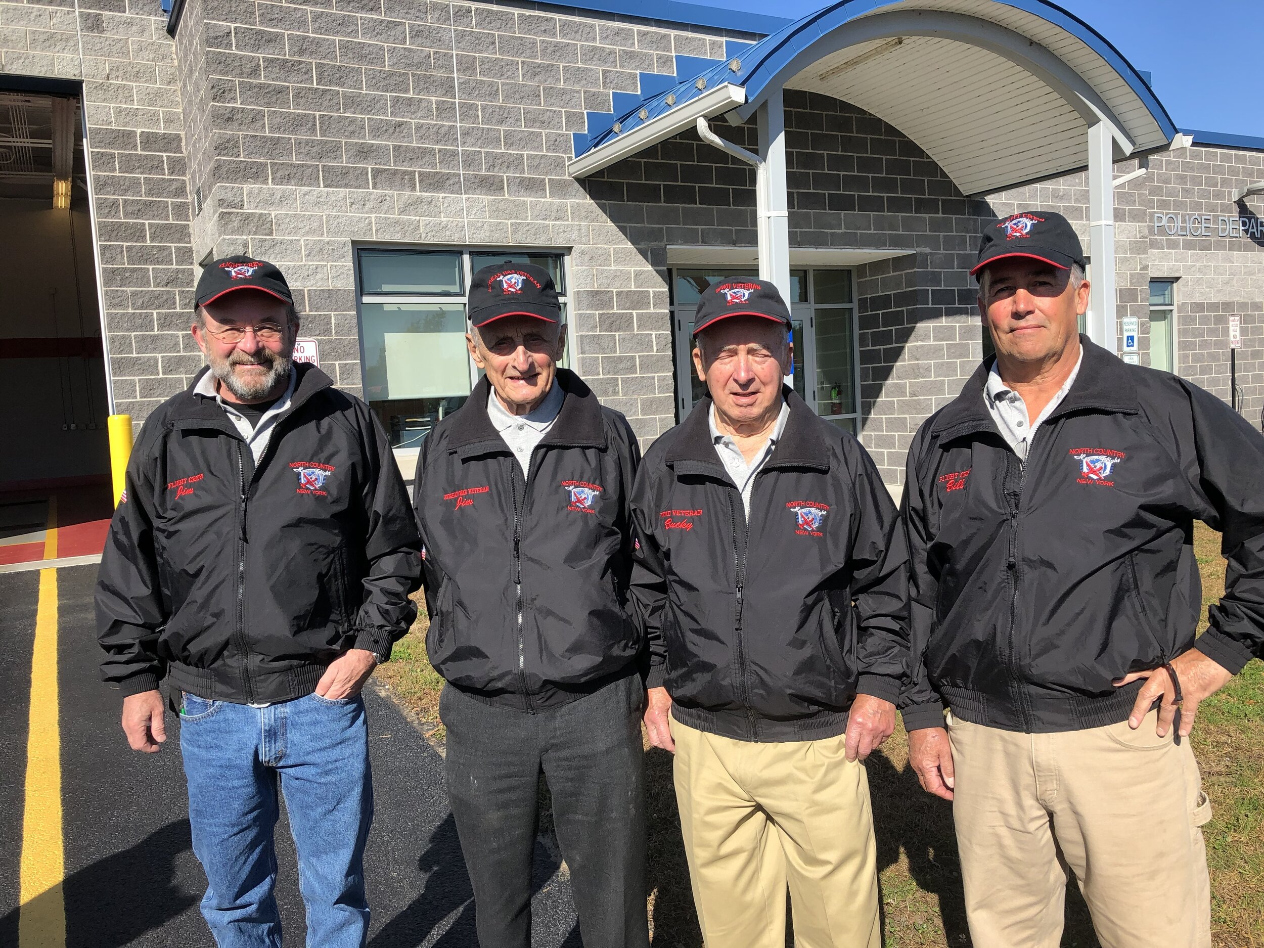 Honor Flight honorees Jim Frenette and Bucky Clark stand outside the village police and fire station with their sons Jim and Bill. (Dan McClelland photos)