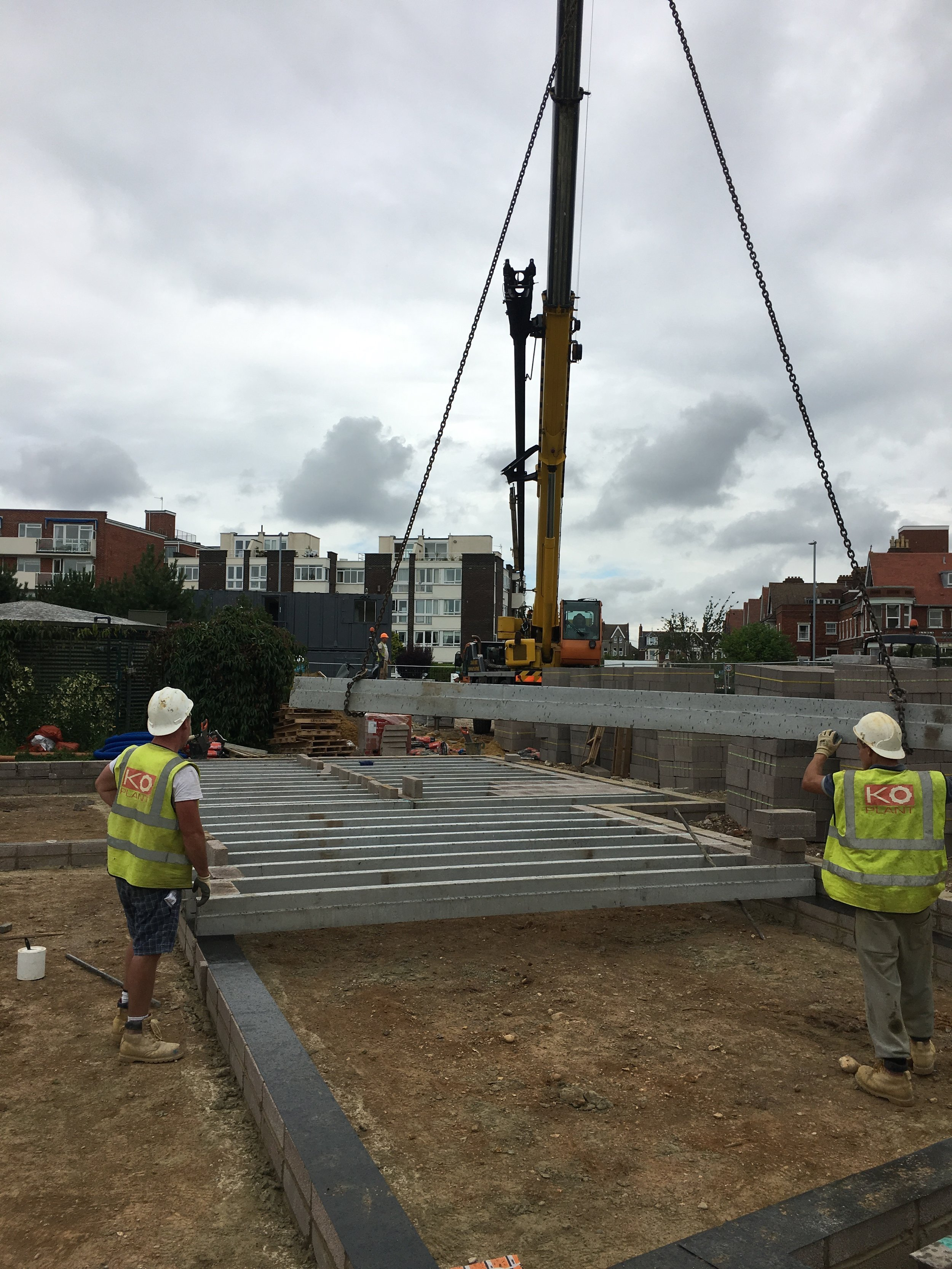 The concrete beam and block slab is lifted into place and assembled