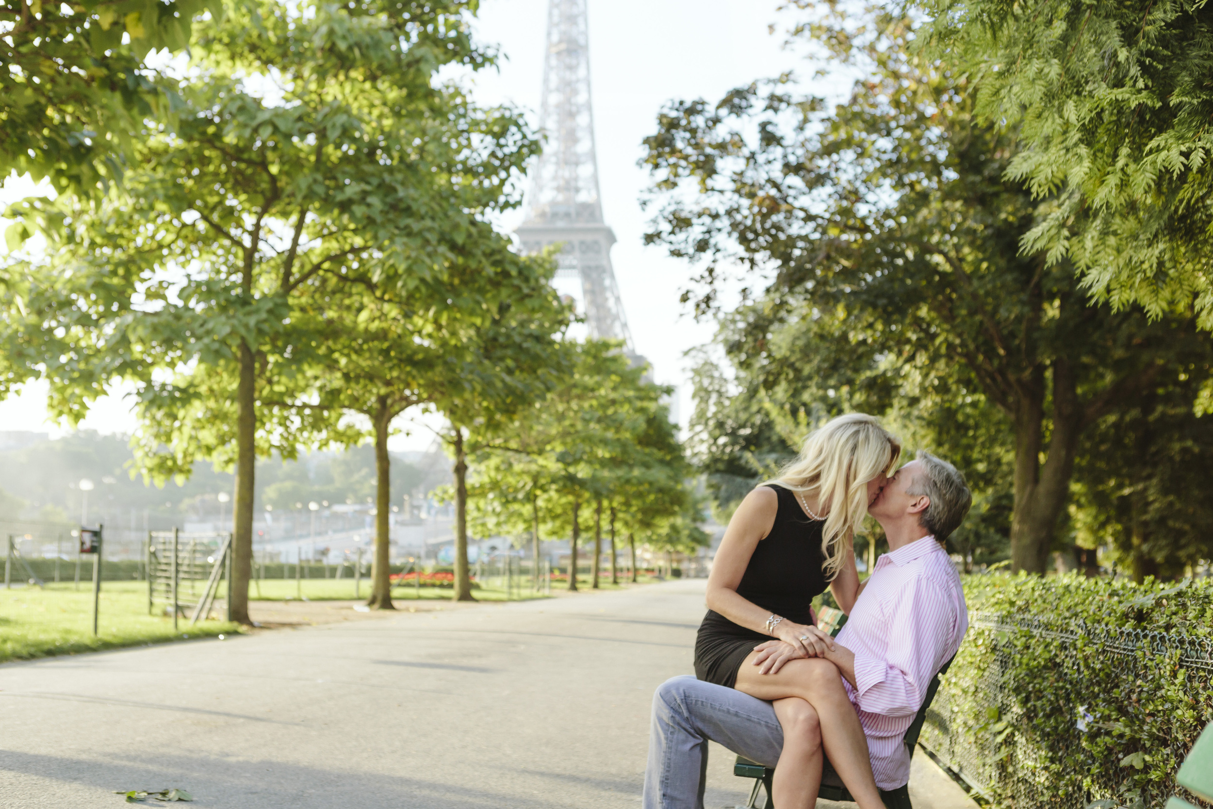 paris photographer couple kissing on a bench by the eiffel tower at trocadero